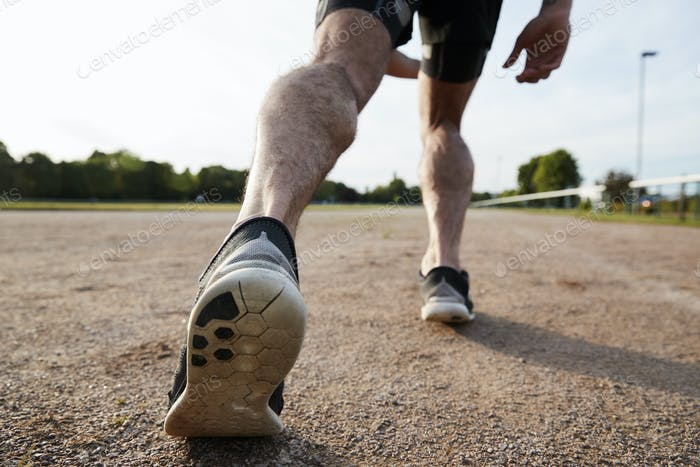 Low section of male runner's legs ready to run at a track