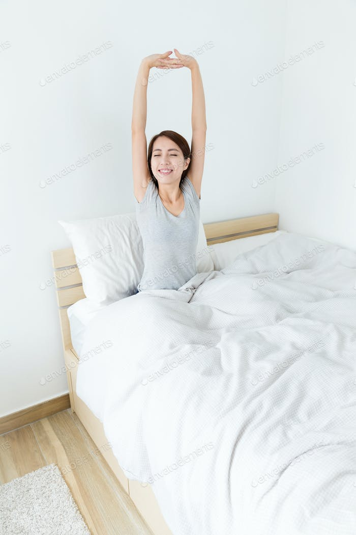 Young girl sitting on bed and hand raised up