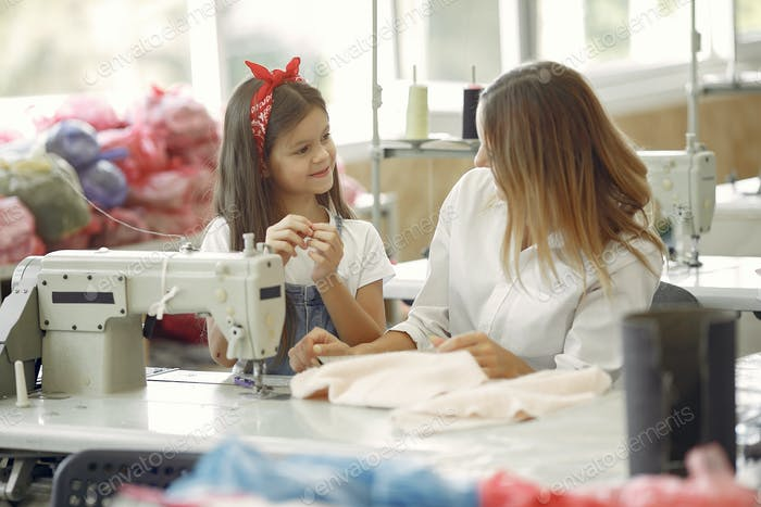 Mother with little daughter sew clothes in the factory