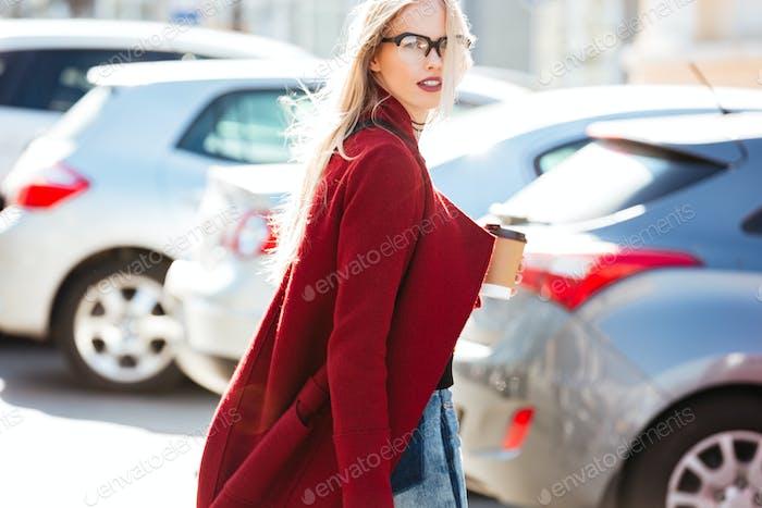 Beautiful young caucasian woman walking outdoors drinking coffee.
