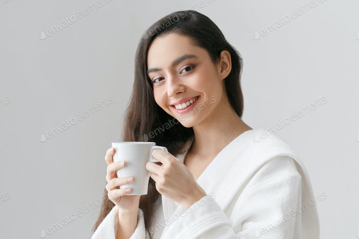 Beautiful woman with cup in hands at home, drink tea or coffe