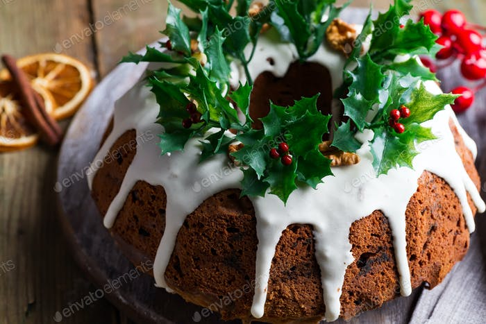 Christmas chocolate cake with white icing and pomegranate kernels on a wooden dark background