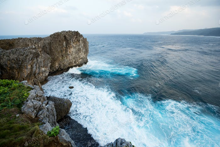 Waves crashing over rock formation cliff