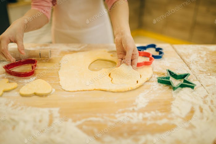 Little girl makes cookies in the shape of a heart