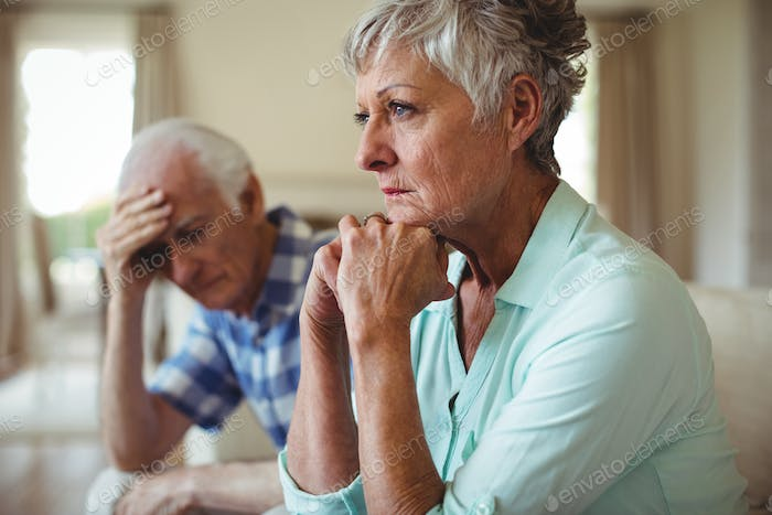 Upset senior couple relaxing on sofa