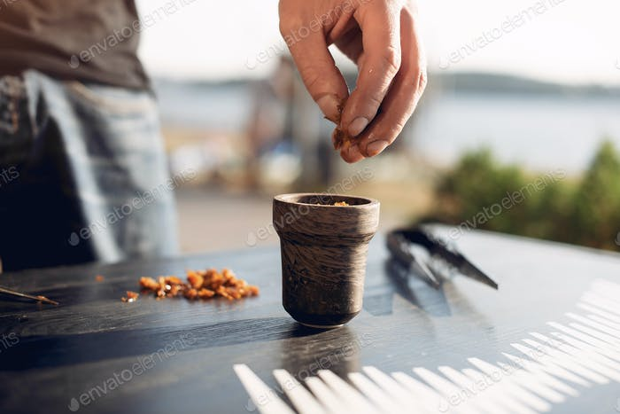 Cropped view of preparing tobacco for shisha on table outside