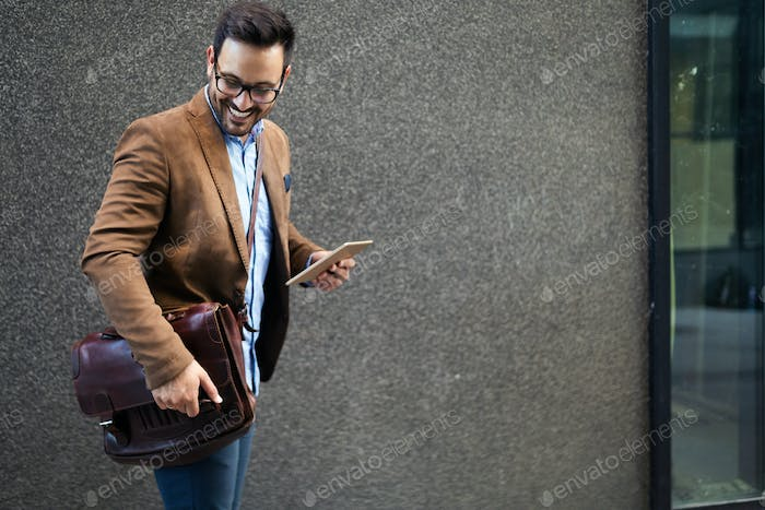 Happy businessman outside of office in urban. Young caucasian man holding tablet for business work