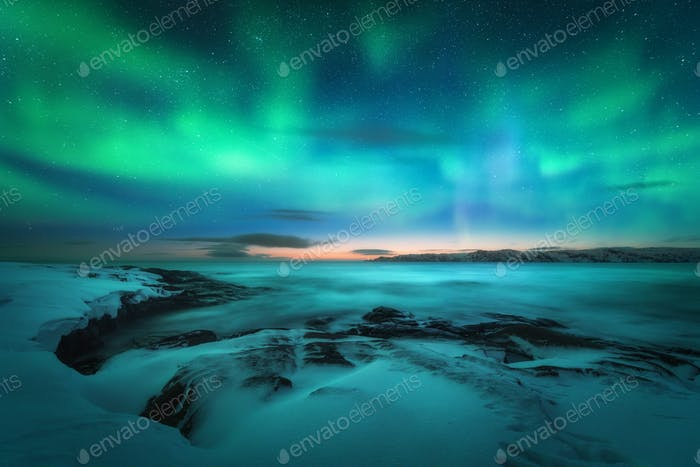 Aurora borealis over rocky beach and ocean. Northern lights
