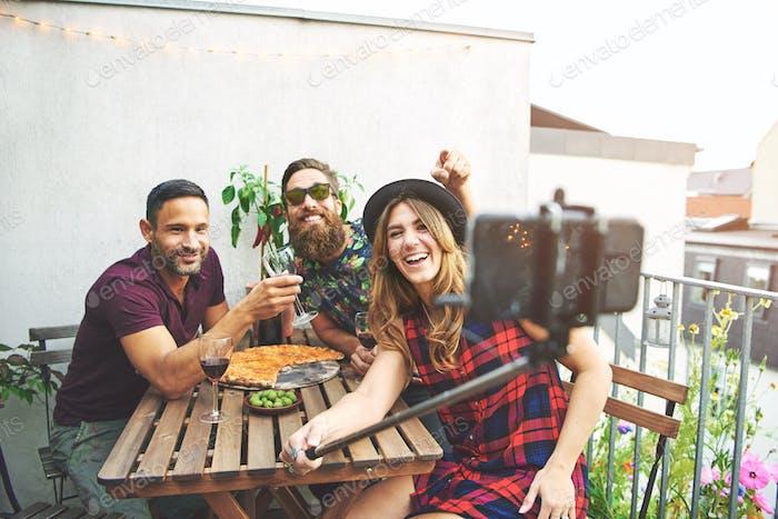 Freunde mit Pizza und Wein nehmen Selfies