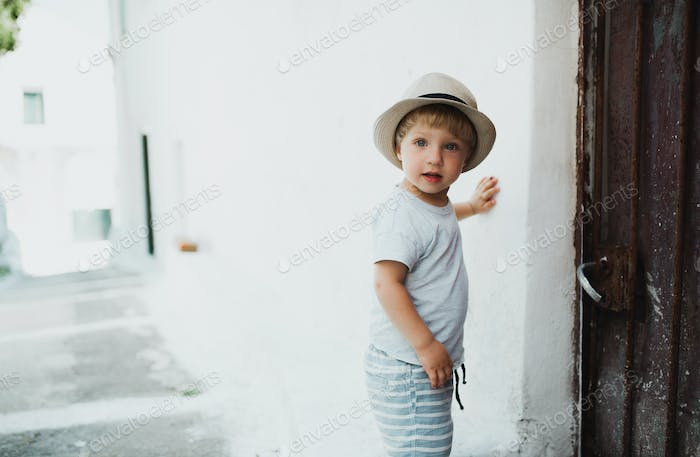 A small toddler boy with hat standing by a house in town on summer holiday.
