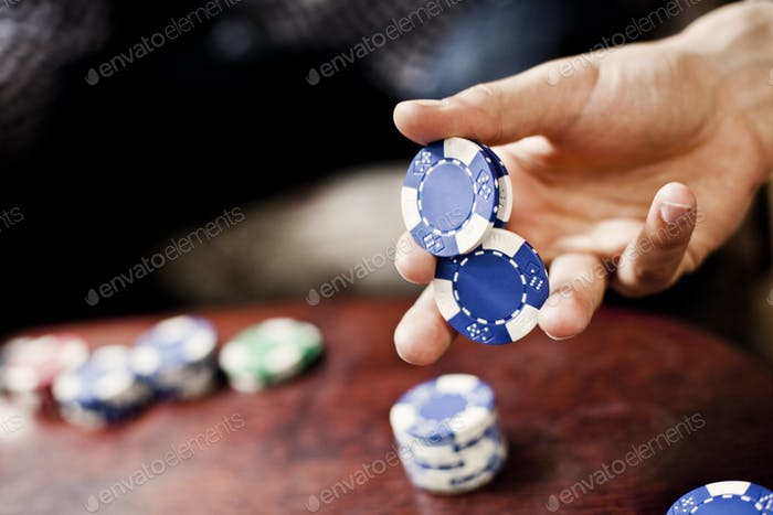 Cropped image of hand holding poker chips at casino table