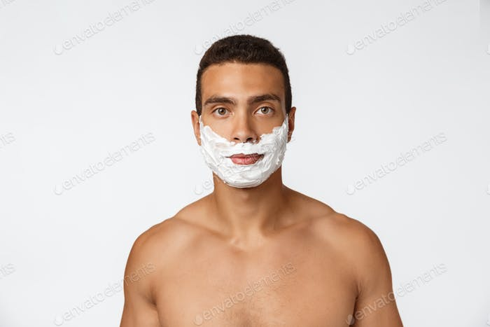 Close up of a happy naked african man with face in shaving foam isolated over gray background