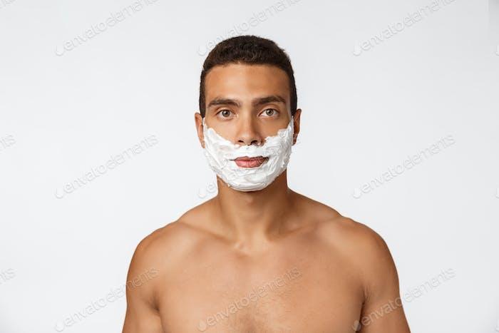Nahaufnahme von einem glücklichen nackten afrikanischen Mann mit Gesicht in Rasierschaum isoliert über grauen Hintergrund