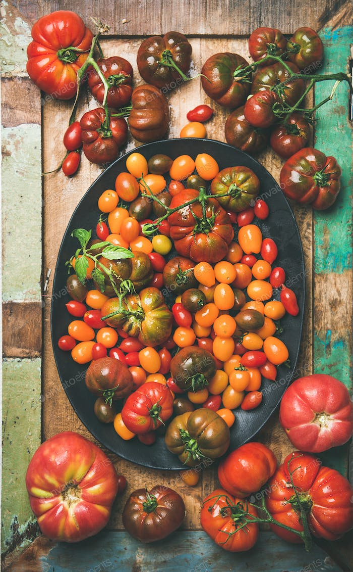 Flat -lay of fresh colorful tomatoes on plate, vertical composition