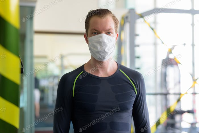 Young man with mask for protection from corona virus outbreak at gym during corona virus covid-19