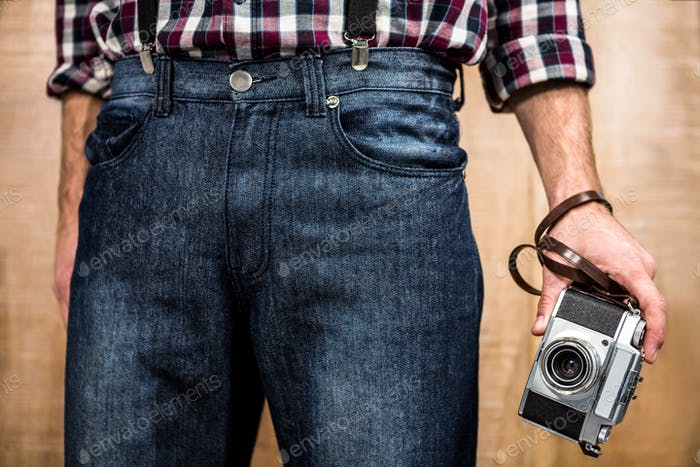 Hipster man holding digital camera with wooden background