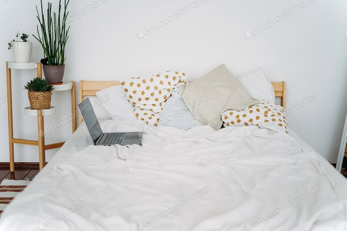 Opened laptop notebook on bed at bright scandinavian interior