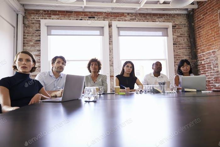 Бизнесмены, слушающие презентацию в зале заседаний