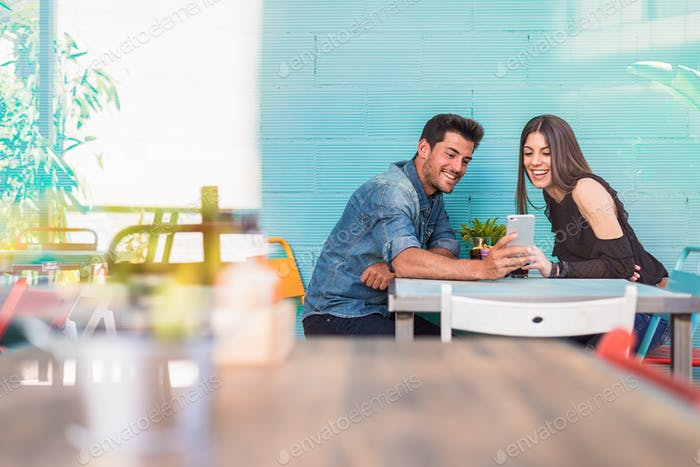 Happy young couple seating in a restaurant with a smartphone