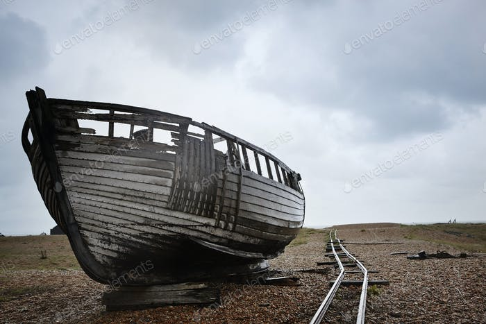 Abandoned wooden boat beached on the shingle near old narrow gauge rails.