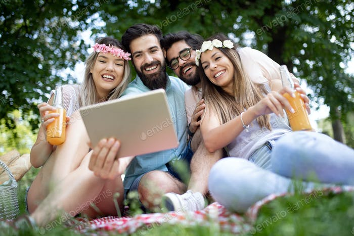 Happy young friends taking selfies on a picnic outdoor