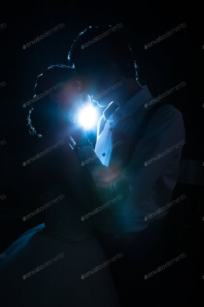 Beautiful inlove bride and groom backlit with blue light