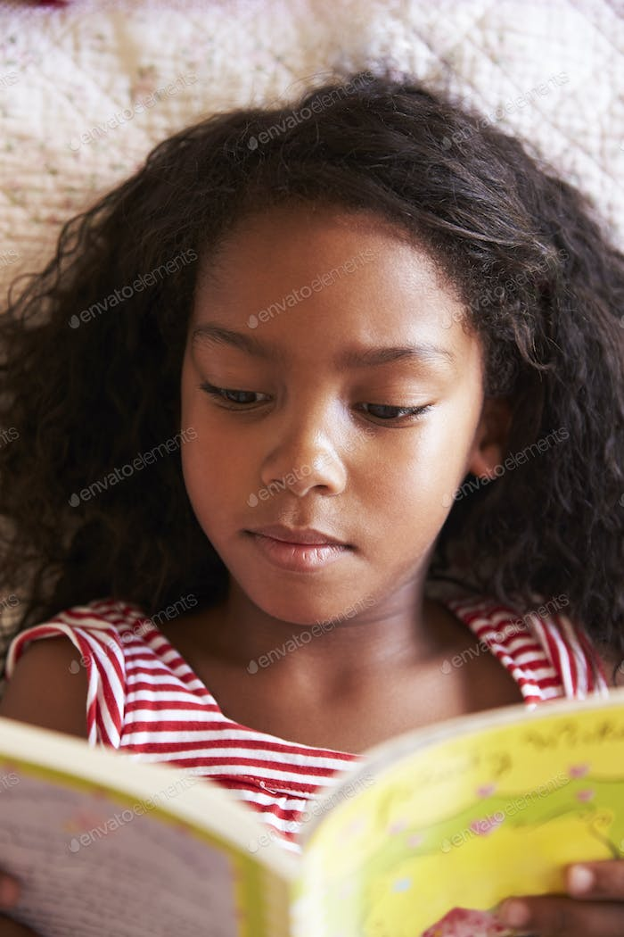 Overhead View Of Girl Lying On Bed And Reading Book