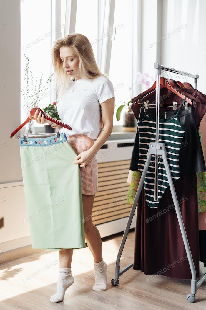 Hermosa joven escogiendo ropa