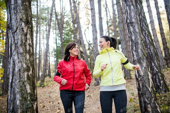 Female runners with earphones and smartphones jogging outdoors in forest.