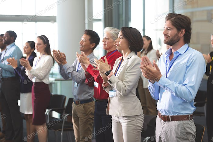 Side view of diverse business people applauding standing at a business seminar in office building