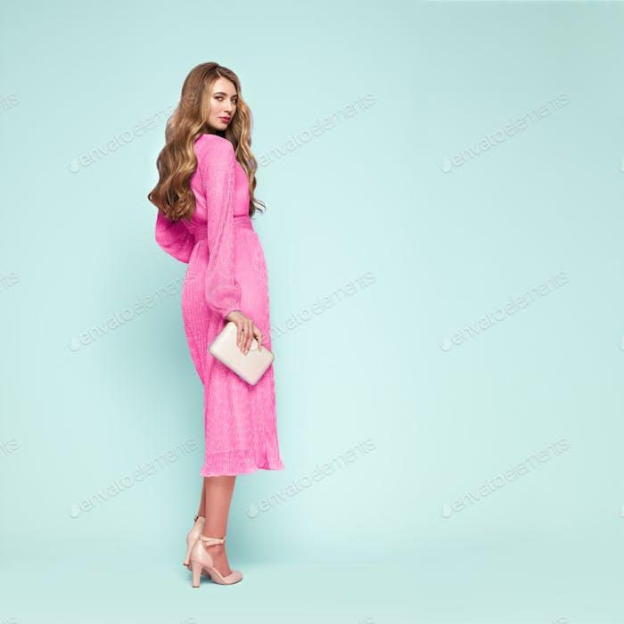 Blonde junge Frau in eleganten rosa Kleid