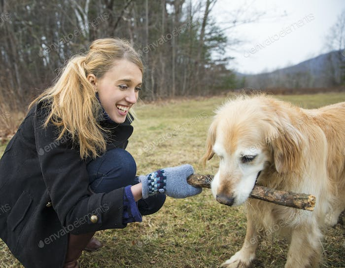 A young woman outdoors in the winter, on a walk with a golden retriever dog.