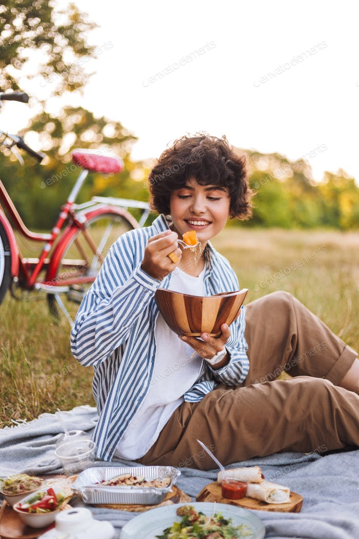 Cute girl in striped shirt sitting on blanket eating salad on pi
