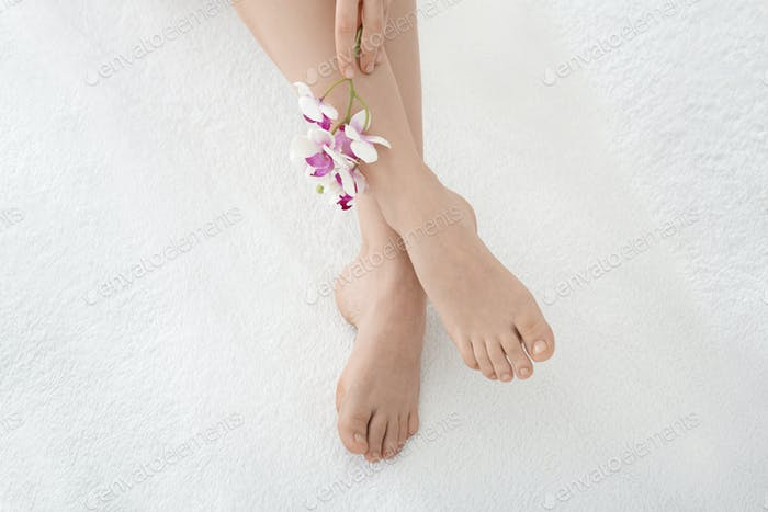Beautiful legs concept. Female well-groomed legs and pedicures with flower
