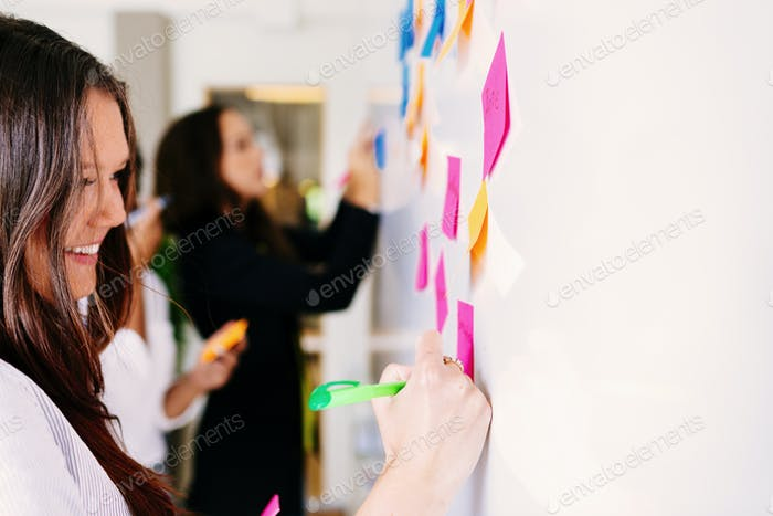 Businesswomen fixing sticky notes at office