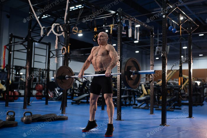 Determined elderly man lifting barbell in contemporary gym