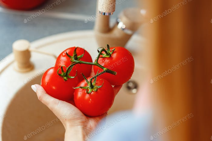 Unrecognizable woman washing fresh tomatoes in sink