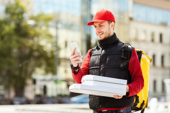 Courier With Pizza Boxes Using Phone Delivering Food In City
