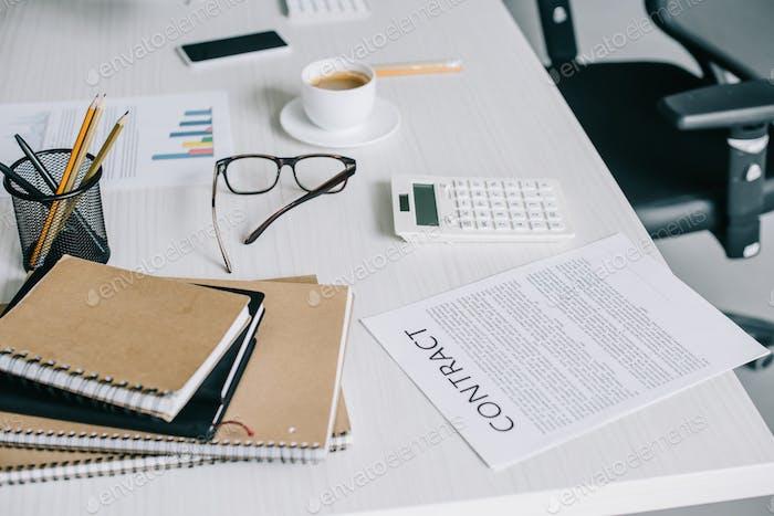 cuadernos, contrato y calculadora sobre mesa en oficina moderna y ligera