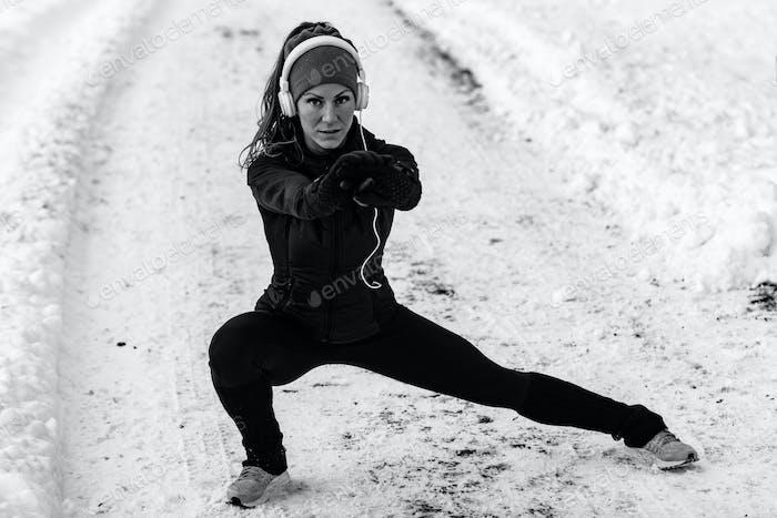 Female athlete exercising in park in winter