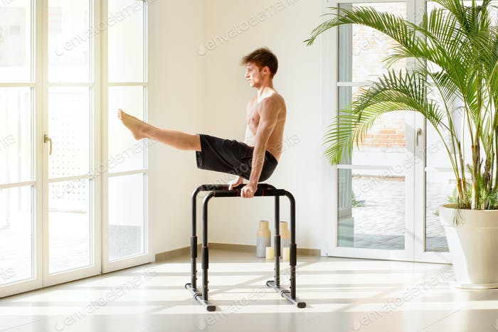 Fit young man working out on parallel bars