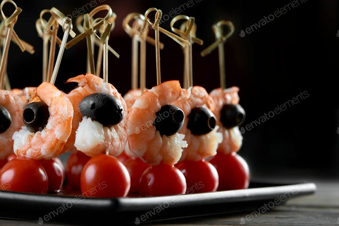 Tasty shrimps appetizer on the dark background