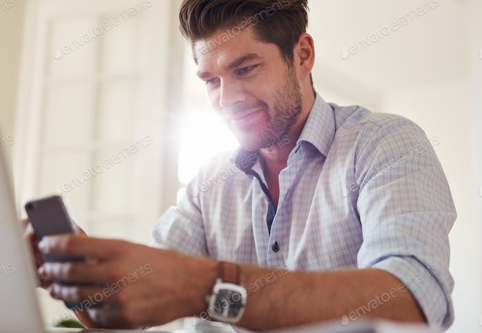 Handsome young man at home using mobile phone