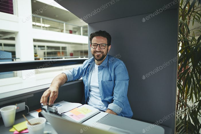 Smiling designer working inside of an office meeting pod
