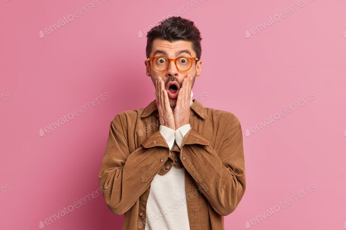 Stunned Caucasian man keeps hands on cheeks opens mouth from wonder stands indoor poses in brown shi