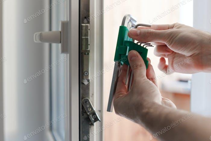 Man's hand choose allen key for adjustment of hardware of the uPVC door mechanism