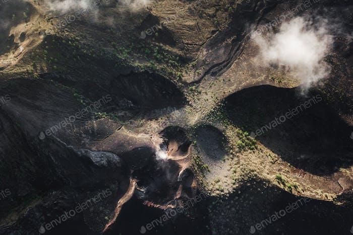 Aerial view of Batur volcano caldera in Bali. Volcanic black texture and crater rim