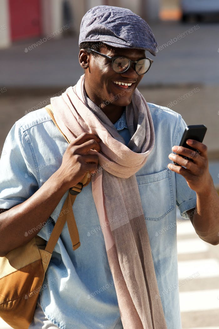 cheerful young man with glasses and cap looking at mobile phone and smiling