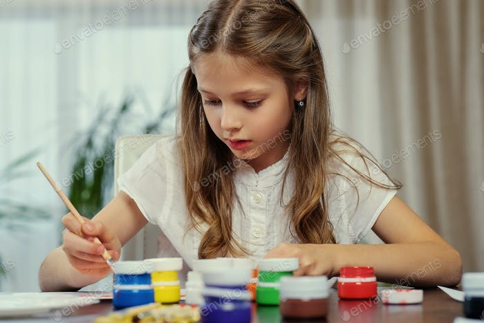 A  girl painting with acrylic paint.