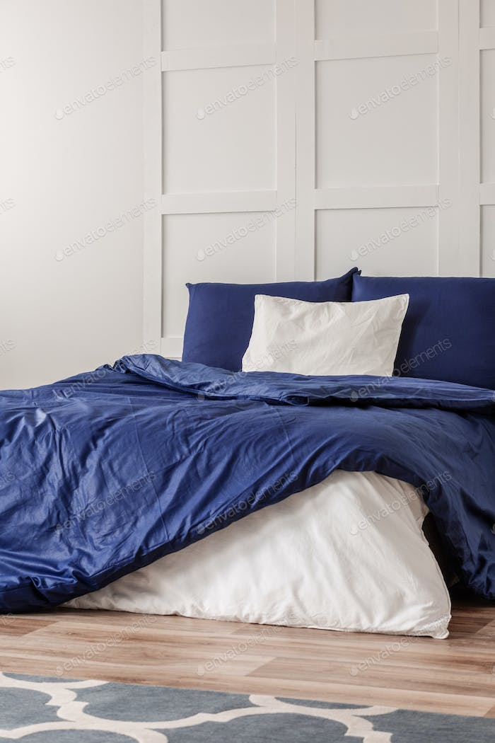 White pillow in the middle of king size bed with blue duvet, copy space on empty wall